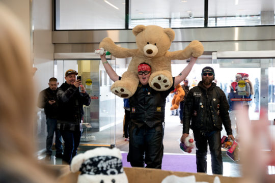 Alissa Davis enters the atrium of the children's hospital with a giant teddy bear to donate Dec. 3 during the 32nd Annual Children's Hospital Colorado Toy Run. This is Alissa's second year participating in the event, where thousands of motorcyclists meet