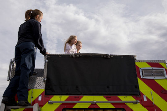 With the help of Marissa Gettman, left, Jolee, center, and Joseph Battaglia-Madrid, get a view from the top of a fire engine, Dec. 3 at Aurora Sports Park, before leaving in a convoy heading to Colorado Children's Hospital as part of the 32nd Annual Child