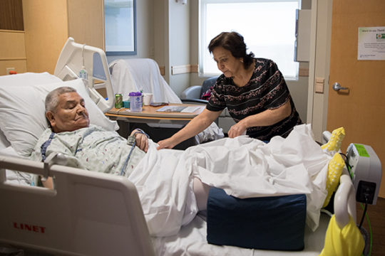 Lupita Hernandez adjusts the sheets on her father's, Antonio Vargas, hospital bed while they wait on the occupational therapist to help get him ready for discharge, Dec. 7 at Parker Adventist Hospital. Vargas was the recipient of a free knee replacement a