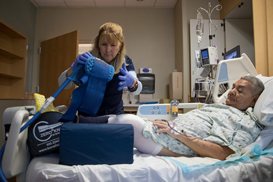Occupational therapist, Lynn Mackay, removes a brace, which stabilized Anotnio Vargas' leg in order to prepare him to be discharged, Dec. 7 at Parker Adventist Hospital. Vargas was the recipient of a free knee replacement after qualifying for the Operatio