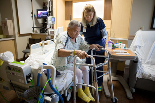 Occupational therapist, Lynn Mackay, helps Anotonio Vargas out of his hospital bed, to prepare him to be discharged, Dec. 7 at Parker Adventist Hospital. Vargas was the recipient of a free knee replacement after qualifying for the Operation Walk USA 2017
