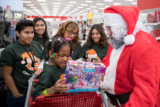 peFrom left, Allison Pacheco, Monserrat Lopez, Perla Guzman and Leticia Vazquez look on as Lansing Elementary student Kynedi Bell, front, shows Santa what she picked out for herself, during the 4th Annual Shop With an Oly event Dec. 9 at the Target on E.
