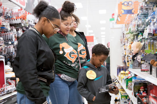 From left, with the help of Gateway Takiah Manlove, Kristina Mitchell and Alyssa Quinlan, Sean Murray, student at Jewell Elementary, picks out a toy for himself, during the 4th Annual Shop With an Oly event Dec. 9 at the Target on E. Ellsworth Ave. Groups