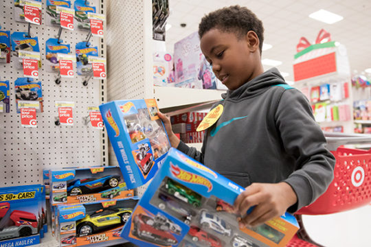 Jewell Elementary School student, Sean Murray, decides which toy car set he wants during the 4th Annual Shop With an Oly event Dec. 9 at the Target on E. Ellsworth Ave. Four Gateway students, who raised $100 per group, were paired up with an elementary sc