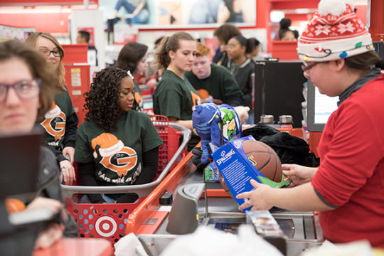 Gateway High School students line up in the check out lane after finishing the 4th Annual Shop With an Oly event Dec. 9 at the Target on E. Ellsworth Ave. Four Gateway students, who raised $100 per group, were paired up with an elementary school student f