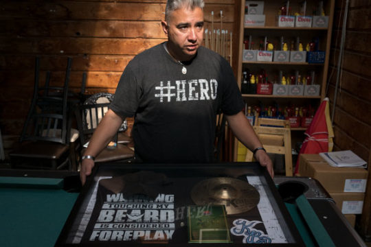 Tim Robles shows off a shadow box that friends and fellow co-workers made in remembrance of Kelly Acosta, which features some of his personal belongings and favorite things, Aug. 14 at the Emerald Isle. Kelly, who was an employee at Emerald Isle, was gunn
