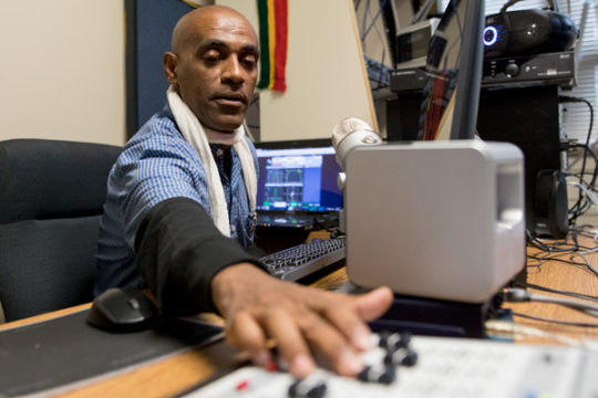 Endale Getahun adjusts the sliders of his mixing board, Oct. 2 in KETO studio, located in an administration building on the Aurora Central High School campus. His  radio station, KETO 93.9, went live on Sept. 11 2017, Ethiopia's independence day, and is t