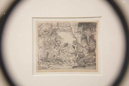 The etching, Adoration of the Shepards with Lamp is seen through a magnifying glass in The Art Gallery of the Fulginiti Pavilion of Bioethics and Humanities. Viewers of the exhibit are encouraged to use the magnifying glasses to give a better view of the