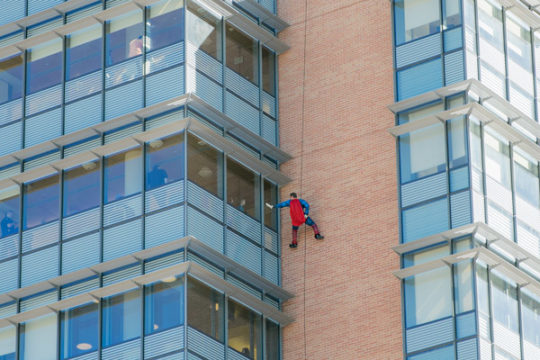 Officer Jeremiah Miles, dressed as Superman, waves to a floor of children, Oct. 17, after rappelling from the rooftop of Children's Hospital. Superhero friends rappelled from the rooftop to surprise patients and their families, stopping at various floors