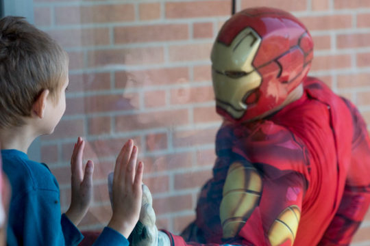 William Blevins, 12, stares out as Iron Man, played by Officer Steve Larson, swings over to the window to say hello, Oct. 17, after rappelling from the rooftop of Children's Hospital. Superhero friends rappelled from the rooftop to surprise patients and t