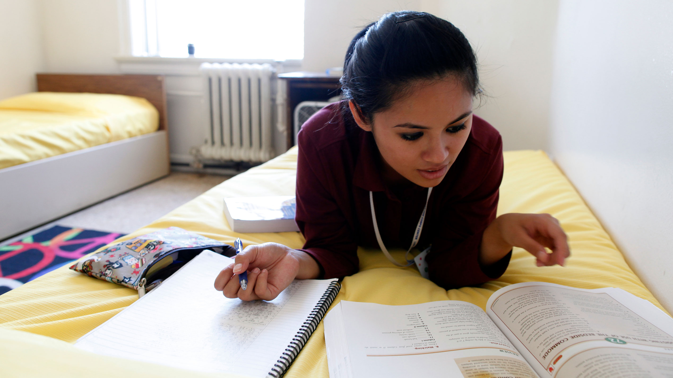Young woman lies on dorm bed studying from a text book