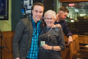 2016-11-16-dr-travis-doucette-with-a-woman-receiving-a-cash-prize-at-the-bha-help-pay-the-rent-event-2