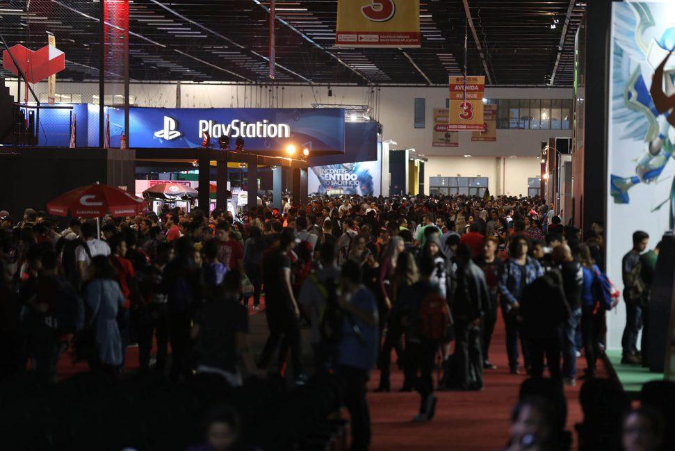 Foto dos corredores entre os expositores. Grande público. Em destaque estande da Playstation.