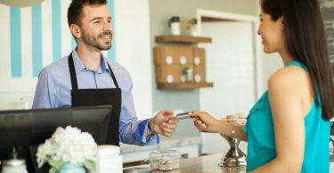 Cliente entregando cartão vale refeição no restaurante para o atendente do caixa