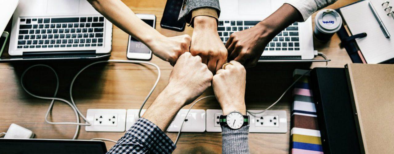 funcionários com as mãos unidas como um time