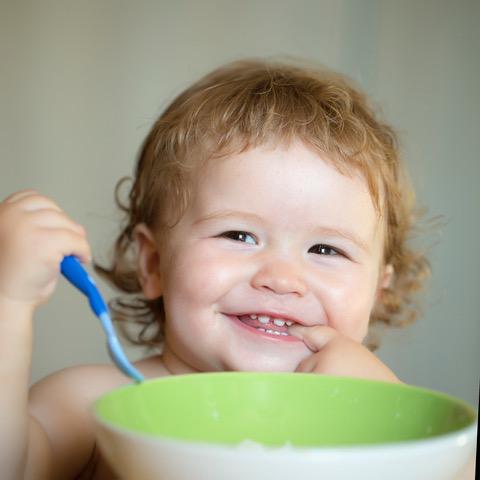 Portrait of funny little smiling boy with blonde curly hair and round cheecks eating from green plate holding spoon closeup, square picture