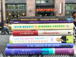Book stack of reads for National Poetry Month at Busboys and Poets