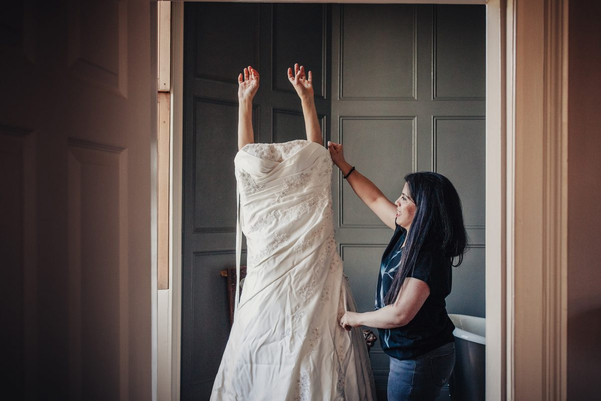 Wedding Photography Backwell House Bristol_bride putting on dress
