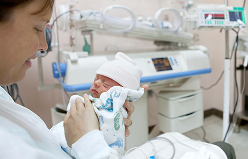 nurse with baby and incubator in background
