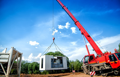 red mobile crane with premanufactured piece of building