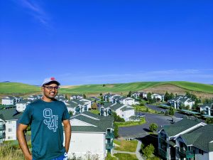 Atit standing on a hill overlooking apartment buildings in the Palouse.