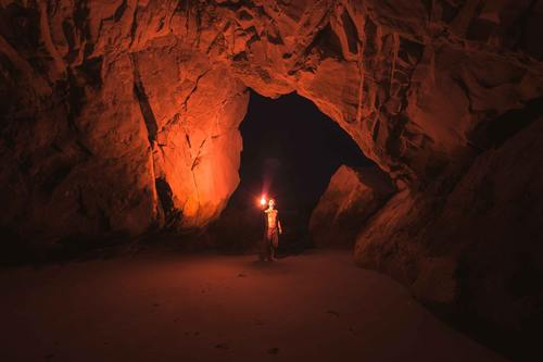 Person standing and holding lamp inside cave 2397414