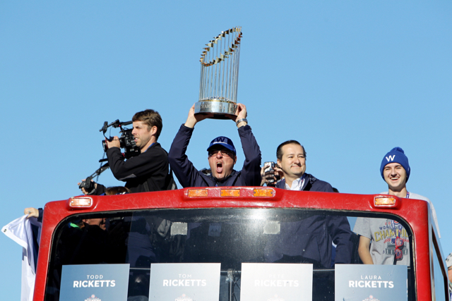 Joe Ricketts hoists the World Series trophy with Chicago Cubs Chairman Tom Ricketts during the 2016 World Series victory parade. (Photo by Dylan Buell/Getty Images)