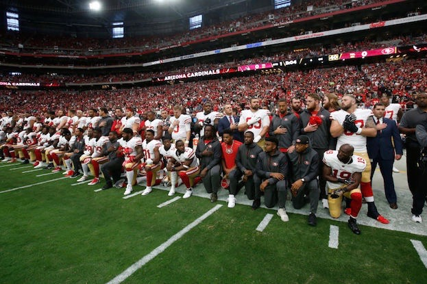 The San Francisco 49ers kneel during the national anthem in protest. (Photo by Michael Zagaris/San Francisco 49ers/Getty Images)