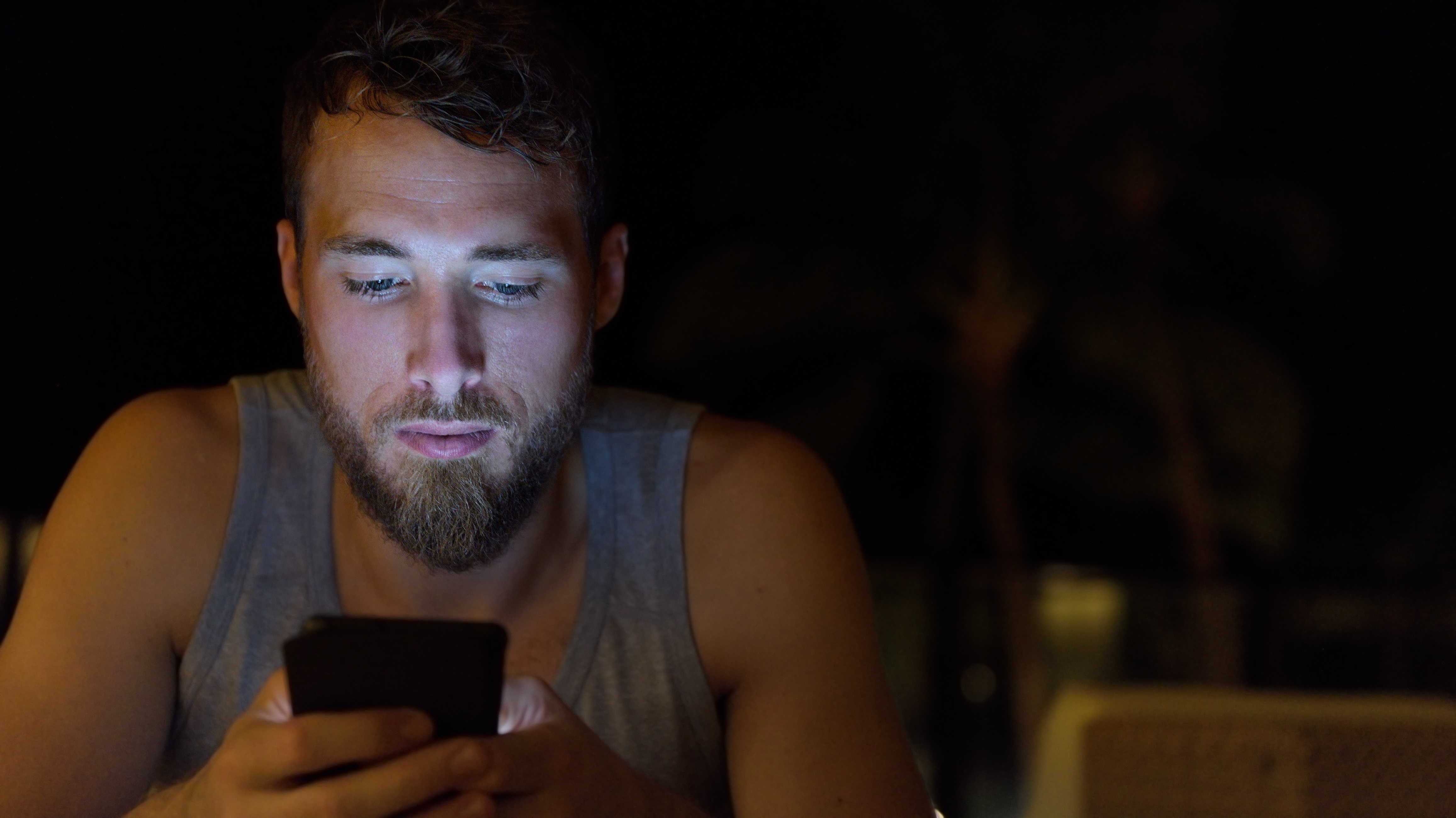 Man using smartphone at night browsing internet updating social media. Young male with beard using mobile cell smart phone outdoors in the dark in summer.