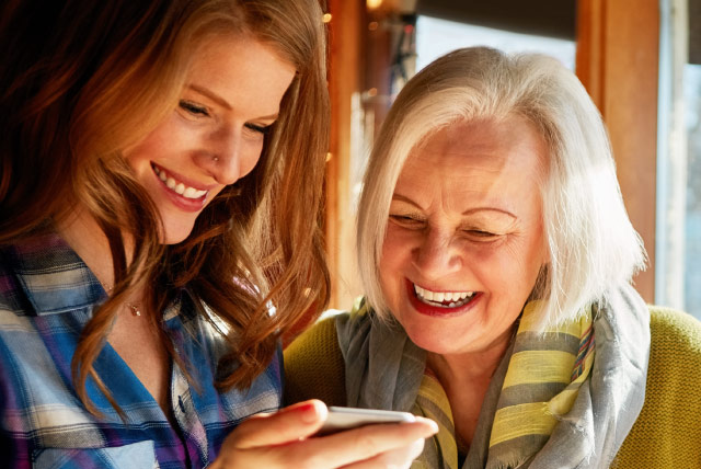Two women smiling while looking at mobile device