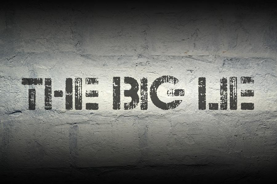 the big lie stencil print on the grunge white brick wall