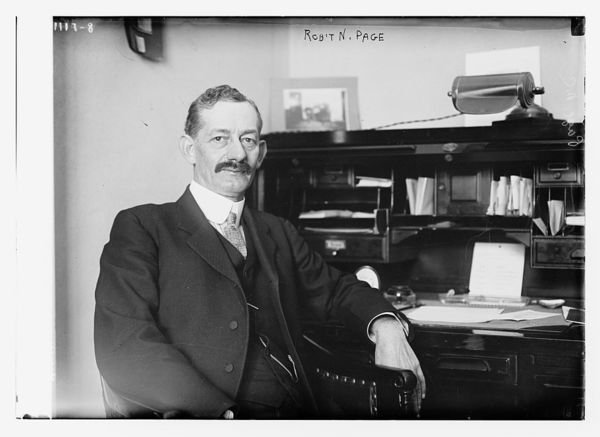 Robt. N. Page seated at desk