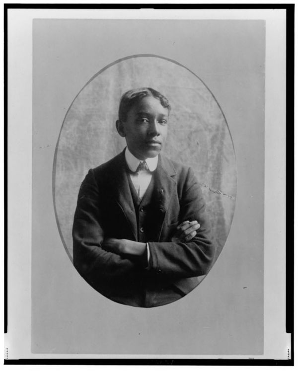 Young African American man, half-length portrait, with arms crossed, facing front