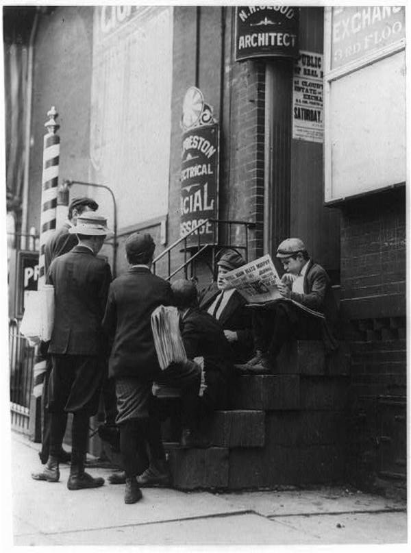 "Group of newsboys on a stoop at 4th & Market Sts. ""Take our mugs, mister?"" Investigator, Edward F. Brown.  Location: Wilmington, Delaware