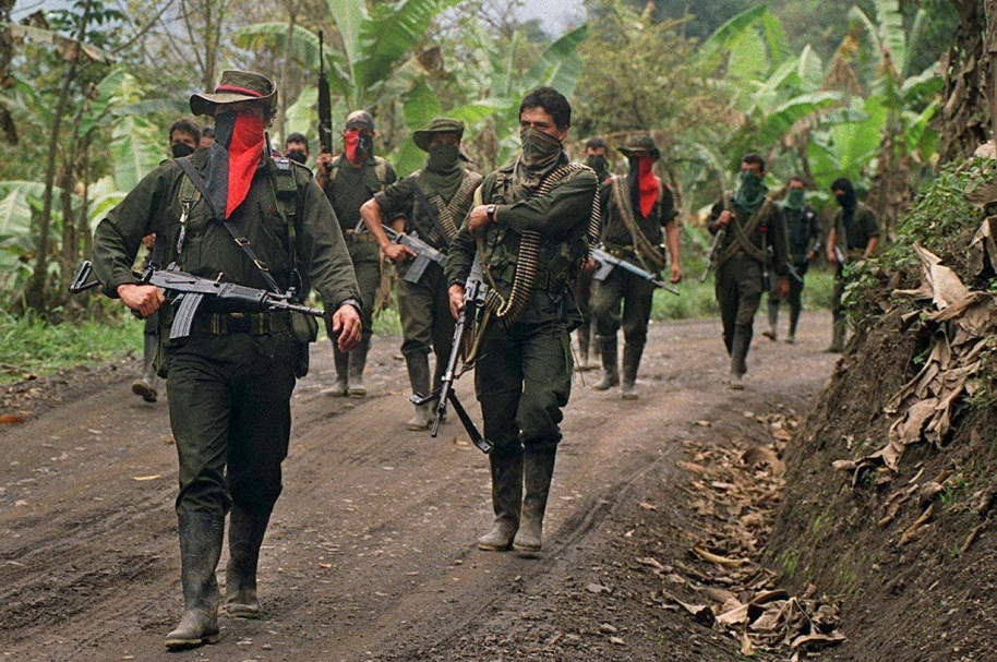 "Members of the Colombian guerrilla movement National Liberation Army (ELN) patrol a rural road in Sarare 27 February 2000 in support of the u'was indian protest against the multinational company OXI planning oil exploration on their sacred indian grounds.    Miembros de la guerrillera del Ejercito de Liberacion Nacional (ELN) patrullan un paraje rural en la zona de la carretera del Sarare, el 27 de febrero de 2000, durante una jornada de ""paro armado"" a la que llamaron en esta zona del Norte de Santander, para apoyar la protesta indigena de los u'was en contra de la multinacional OXI, que pretende realizar excavaciones en esas tierras consideradas sagradas por los indigenas. AFP PHOTO STR / AFP / STR"