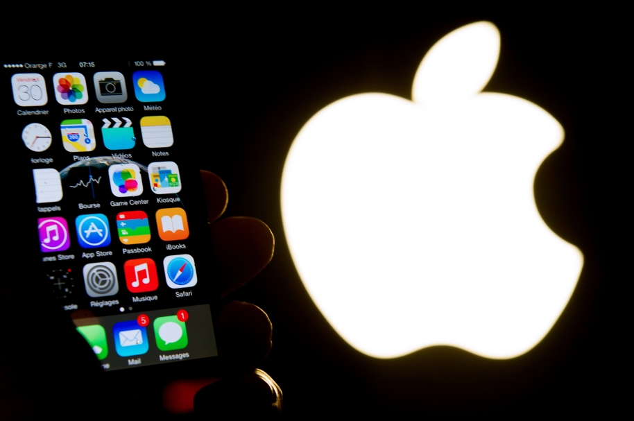 "(FILES) This file photo taken on January 30, 2015 shows an illustration of an iPhone held up in front of the Apple Inc. logo in Lille, France. Apple fired anew March 5, 2016 at the US government's legal fight to force it to break into an attacker's iPhone, saying the tactic would ""appall"" the country's founders. Apple dug into its legal position in a written filing ahead of a hearing set for March 22nd before a federal judge in Southern California.   / AFP / PHILIPPE HUGUEN"