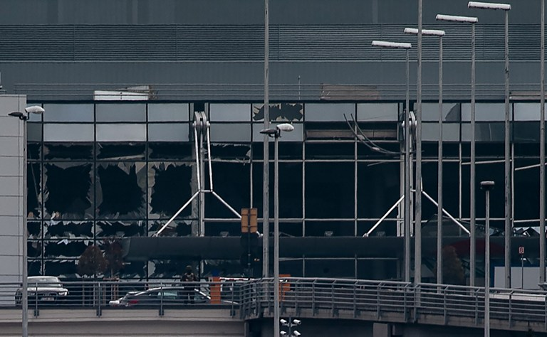 This view taken on March 22, 2016 shows the broken glasses at Brussels Airport in Zaventem after a two explosions targeted the main hall. A string of explosions rocked Brussels airport and a city metro station today, killing at least 13 people, according to media reports, as Belgium raised its terror threat to the maximum level. / AFP / BELGA / JONAS ROOSENS