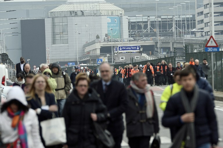 People are evacuated from Brussels Airport, in Zaventem, on March 22, 2016. after at least 13 people have been killed by two explosions in the departure hall of Brussels Airport. / AFP / Belga / LAURIE DIEFFEMBACQ / Belgium OUT