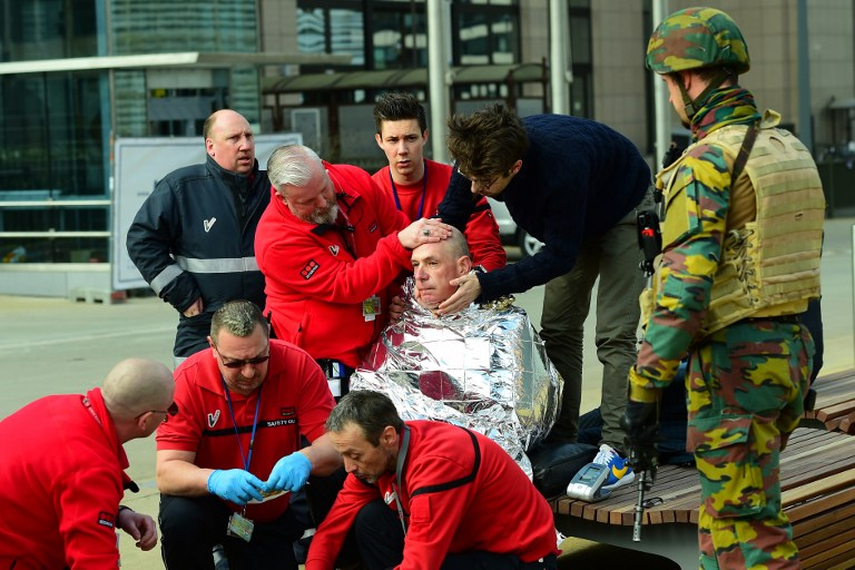 A victim receives first aid by rescuers, on March 22, 2016 near Maalbeek metro station in Brussels, after a blast at this station near the EU institutions caused deaths and injuries. AFP PHOTO / EMMANUEL DUNAND / AFP / EMMANUEL DUNAND