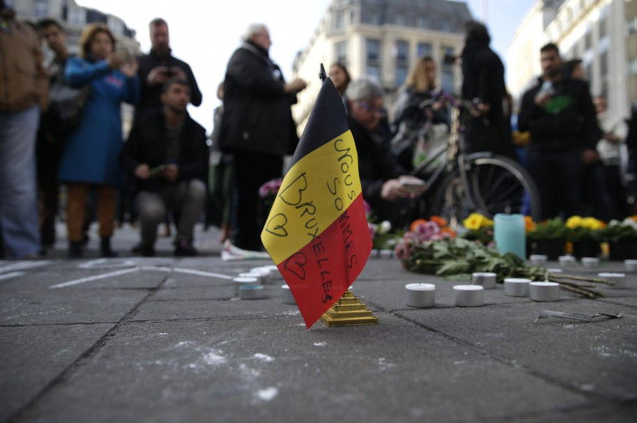 "A Belgian flag reading ""We are all Brussels"" stands at a makeshift memorial at Place de la Bourse (Beursplein) following attacks in Brussels on March 22, 2016. Airlines cancelled hundreds of flights and European railways froze links with Brussels after a series of bomb blasts killed around 35 people in the city's airport and a metro train, sparking a broad security response. AFP PHOTO / KENZO TRIBOUILLARD / AFP / KENZO TRIBOUILLARD"