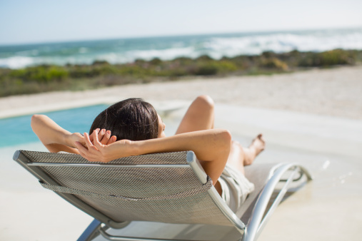 Woman sunbathing on lounge chair at poolside