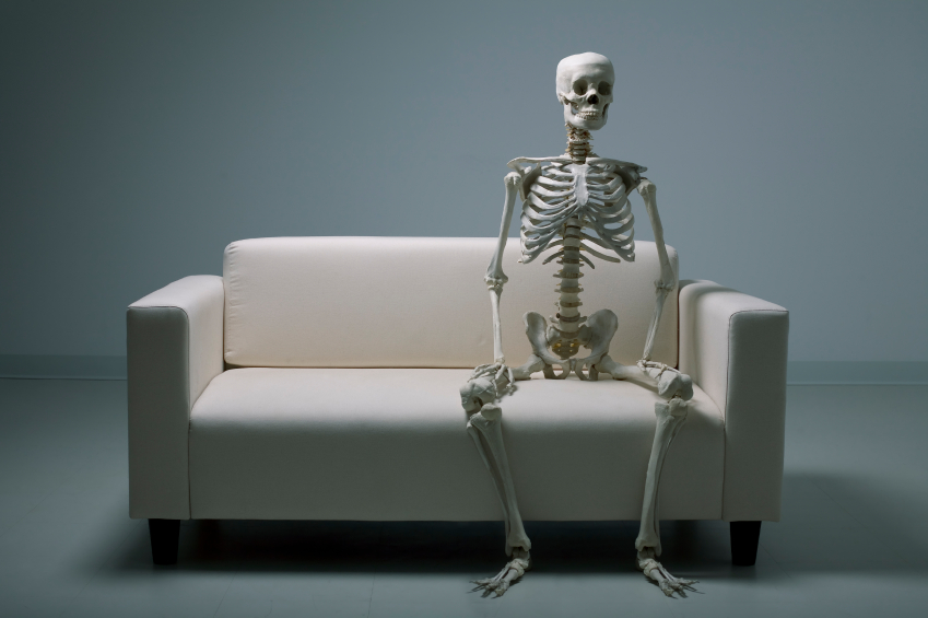 a skeleton sits on a couch.