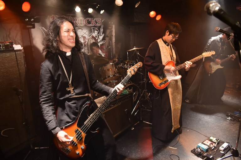 "To go with AFP story Japan-music-religion-lifestyle-offbeat, FEATURE by HARUMI OZAWA This picture taken on September 1, 2015 shows Lutheran pastor Kazuhiro Sekino (L), leader of heavy rock group ""Boxi Rocks"", performing in Tokyo. Most days, Lutheran pastor Kazuhiro Sekino preaches to his congregation in a soft voice with religious hymns playing in the background of a Tokyo church. But as night falls, he hits a smoky stage criss-crossed with whizzing strobe lights, shedding his pious day job in a battle of the bands against a group of Buddhist monks. AFP PHOTO / Yoshikazu TSUNO / AFP / YOSHIKAZU TSUNO"