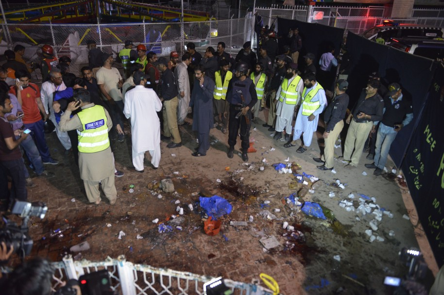 Pakistani rescuers and officials gather at a bomb blast site in Lahore on March 27, 2016.  At least 25 people were killed and dozens injured when an explosion ripped through the parking lot of a crowded park where many minority Christians had gone to celebrate Easter Sunday in the Pakistani city Lahore, officials said. / AFP / ARIF ALI