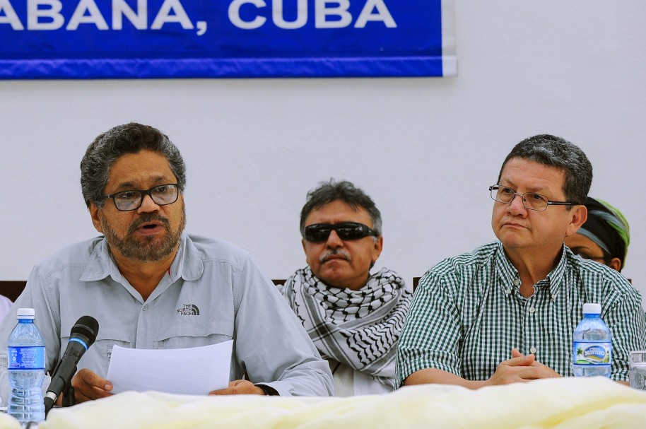 FARC-EP leftist guerrillas commander Ivan Marquez (L) reads a statement next to commanders Pablo Catatumbo (R) and Jesus Santrich (C) in Havana, on July 12, 2015. The Colombian government reached a historic agreement Sunday with leftist FARC guerrillas to de-escalate the decades-long armed conflict, diplomats in Havana said. AFP PHOTO/YAMIL LAGE