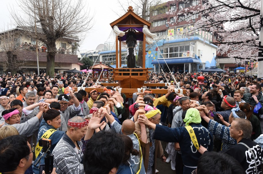 People crowd outside the Wakamiya Hachimangu Shrine to see portable shrines bearing phalluses during the Kanamara Festival in Kawasaki, a suburb of Tokyo on April 3, 2016.  More than 20,000 people gathered to enjoy the annual festival which Shinto believers carry giant phalluses through the streets. / AFP / TORU YAMANAKA