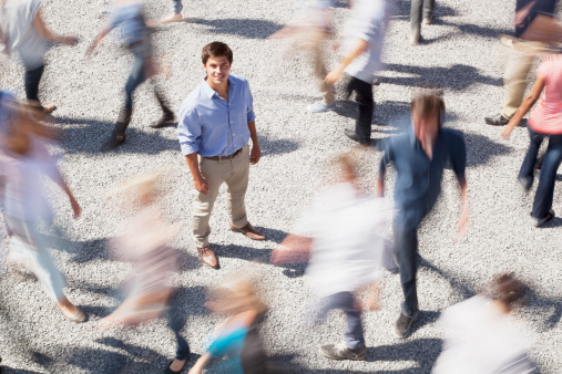 Portrait of smiling businessman surrounded by people rushing by