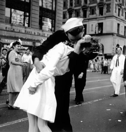 US sailor bending young nurse over his arm to give her passionate kiss in middle of Times Square as others look on amused, during celebration of Japan's surrender to Allies at end of WWII.