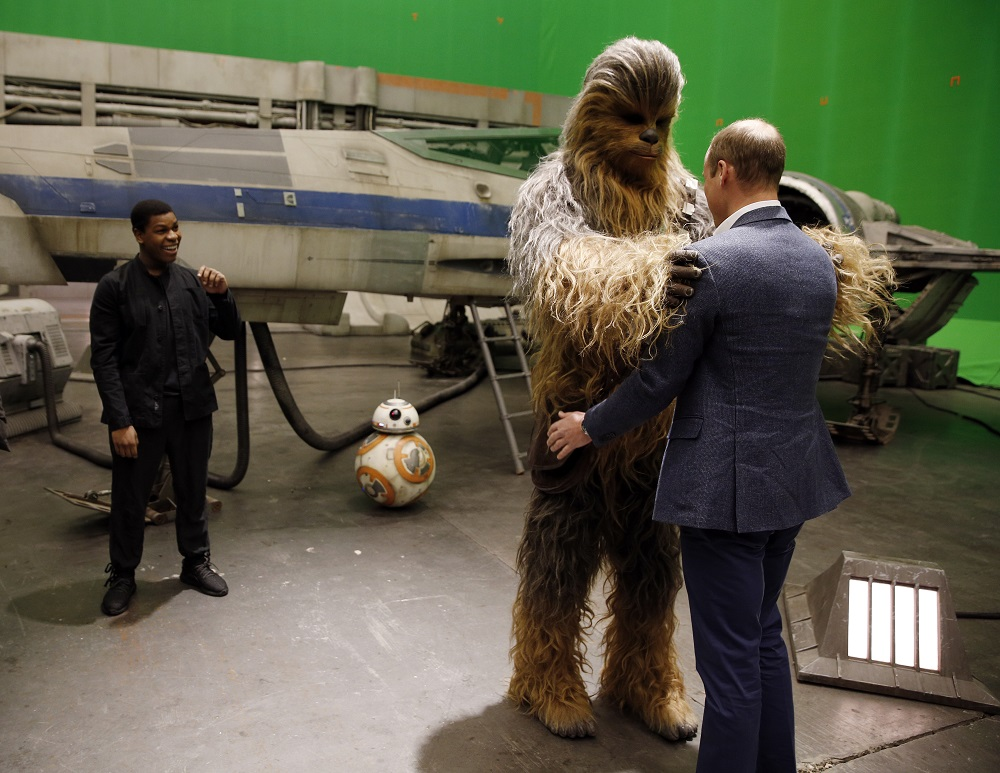 Britain's Prince William, Duke of Cambridge (R) is greeted by Chewbacca during a tour of the Star Wars sets at Pinewood studios in Iver Heath, west of London on April 19, 2016. Prince William and Prince Harry are touring Pinewood to visit the production workshops and meet the creative teams working behind the scenes on the Star Wars films. / AFP PHOTO / ADRIAN DENNIS