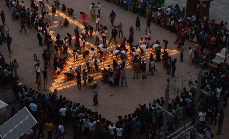 Nepalese residents gather to light candles during a vigil to mark the first anniversary of a devastating earthquake in Durbar Square in Kathmandu on April 24, 2016. Nepal on April 24 held services remembering thousands of people killed in a devastating earthquake one year ago, as authorities vow to expedite long-delayed reconstruction projects. Some 9,000 people were killed in the 7.8-magnitude quake that struck April 25, 2015 and its aftershocks. / AFP PHOTO / PRAKASH MATHEMA